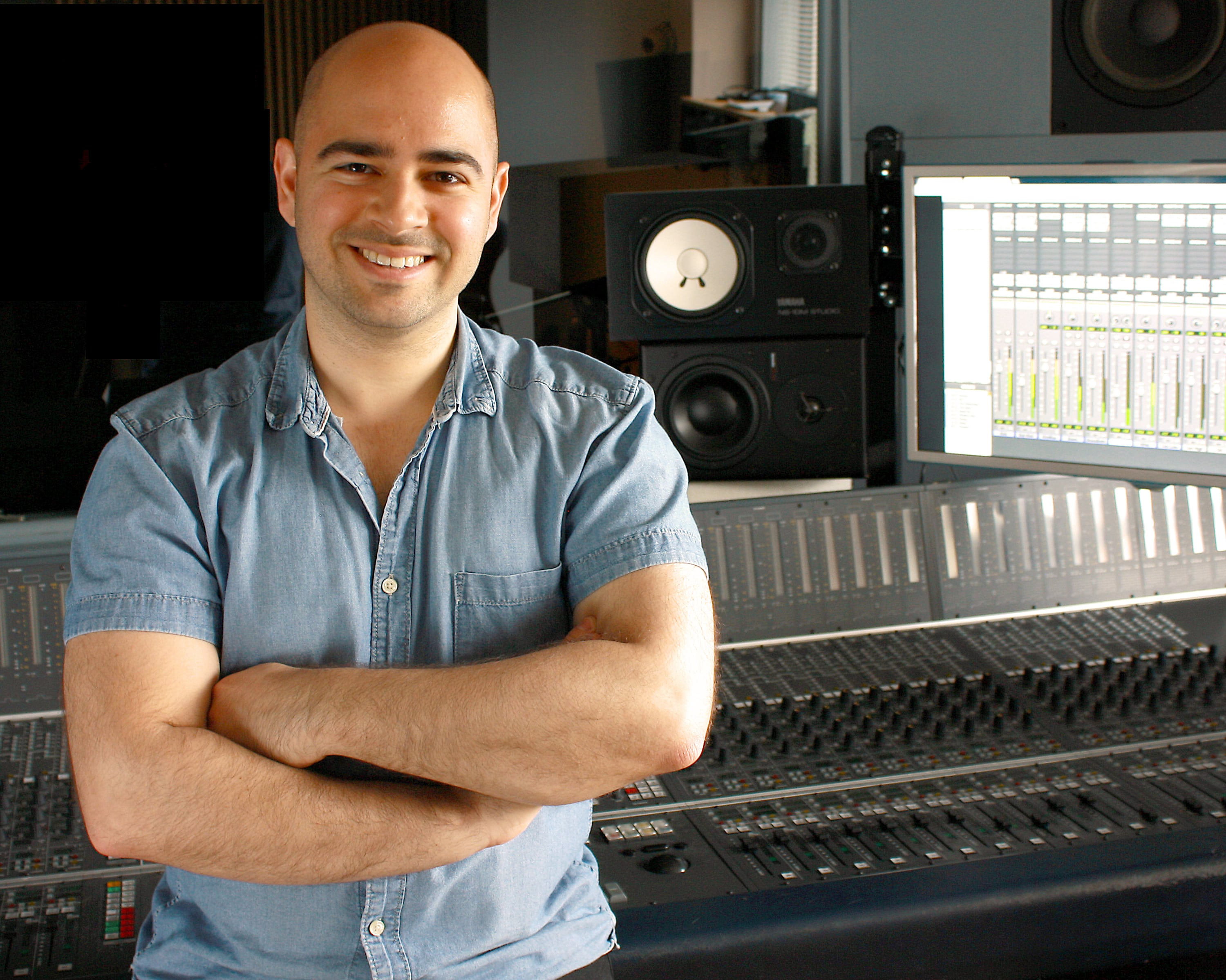 Mike Indovina in front of recording console and speakers